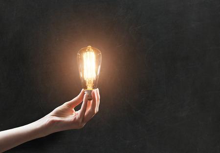 eficiencia energetica: mano que sostiene la bombilla en el fondo pizarra Foto de archivo