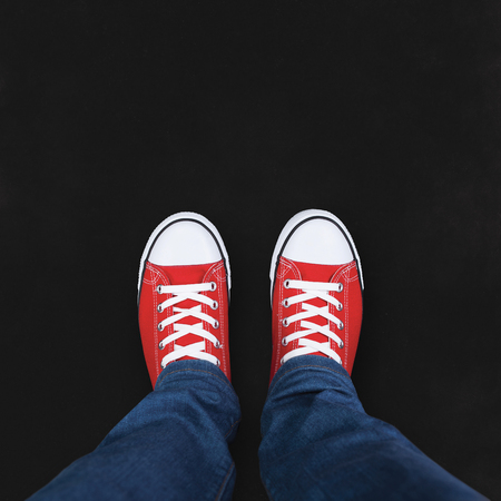 text space: Feet wearing red shoes on black background with space for text