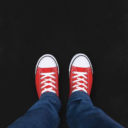 fond de texte: Pieds de porter des chaussures rouges sur fond noir avec l'espace pour le texte