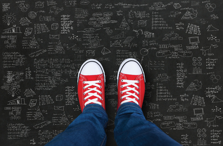 red shoes: Feet wearing red shoes on black background with business plan