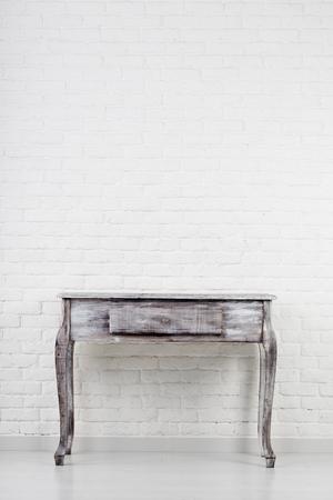 Lege houten tafel over witte bakstenen muur
