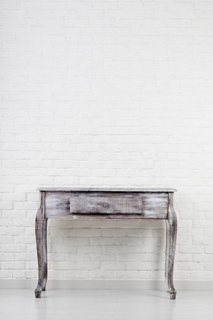 Empty wooden table over white brick wall