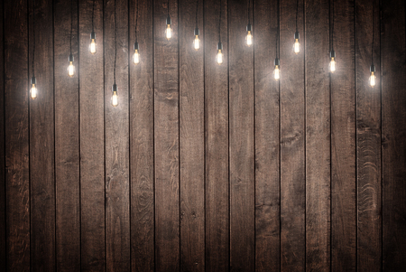 wood floor: Light bulbs on dark Wooden Background Stock Photo
