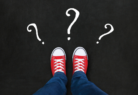 red shoes: Feet wearing red shoes on black background with question marks. choice concept Stock Photo
