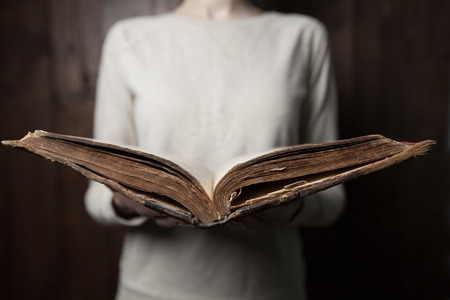 Frau, die Hände auf Bibel. sie liest und betet auf Bibel in einem dunklen Raum über Holztisch Standard-Bild - 50878834