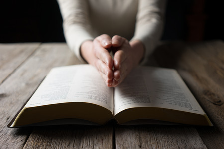 reverent: woman reading the bible in the darkness over wooden table
