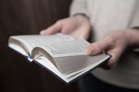 donna mani sulla bibbia. lei sta leggendo e pregando su bibbia in uno spazio buio su tavola di legno Archivio Fotografico