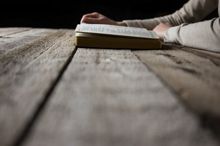 sinner: woman hands on bible. she is reading and praying over bible in a dark space over wooden table