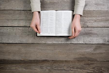 女性は、聖書を手します。彼女は読書で、木製のテーブルの上に聖書を祈る 写真素材