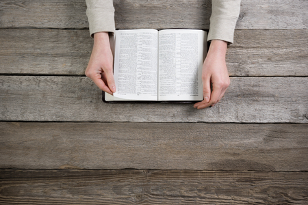woman hands on bible. she is reading and praying over bible over wooden table Stock Photo