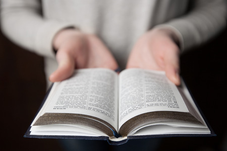holding bible: woman hands on bible. she is reading and praying over bible in a dark space over wooden table