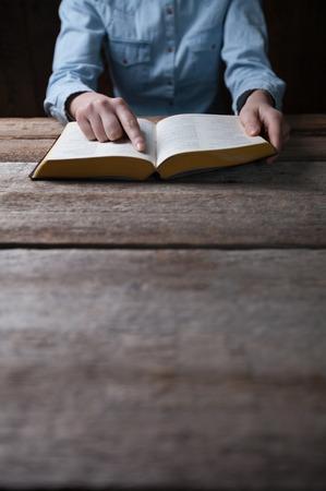 女性は、木製のテーブルの上を暗闇の中で聖書と祈り手します。 写真素材
