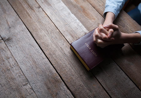 hand of god: hands praying with a bible in a dark over wooden table