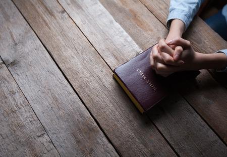 orando manos: manos en oraci�n con una biblia en una mesa de madera oscura sobre
