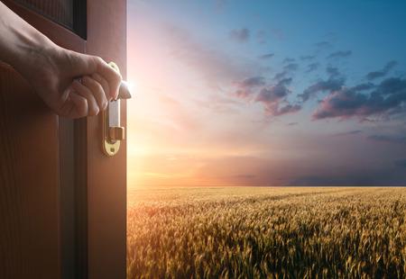 Strony otwiera drzwi do łąki z zieloną trawą i klejem niebo