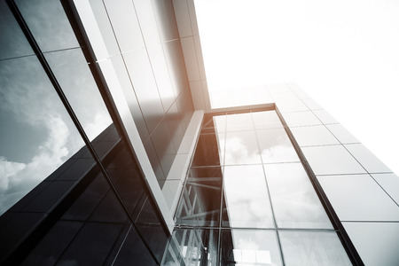 commercial building: Wide angle abstract background view of steel light blue high rise commercial building skyscraper made of glass exterior. concept of successful industrial architecture and office center building Stock Photo