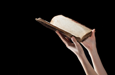 reverent: woman reading the bible in the darkness