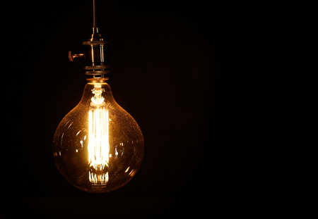 Edison light bulb on black background Imagens