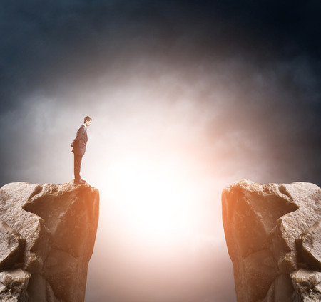 standing businessman: Young businessman standing on edge of rock mountain and looking Stock Photo