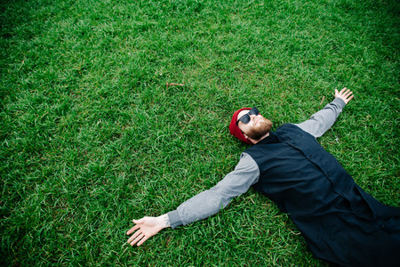 Hipster boy wearing sunglasses and lying on grass Stock Photo
