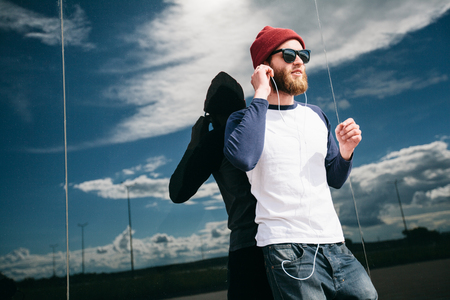 hipster boy listening to music wearing hat