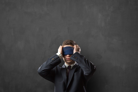 Blindfold businessman over chalkboard or blackboard texture 版權商用圖片
