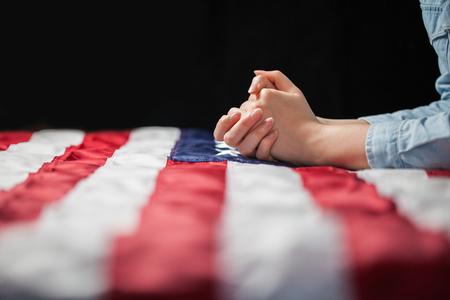 Betende Hände über amerikanische Flagge Standard-Bild - 57482621