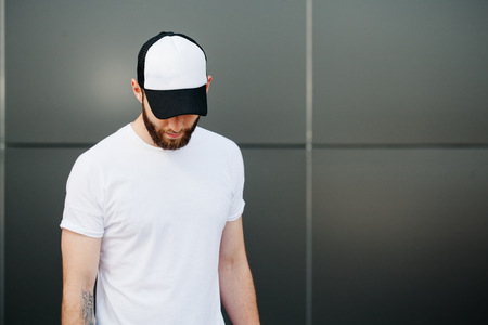 Hipster wearing white blank t-shirt and a cap with space for your logo Stock Photo - 59952158