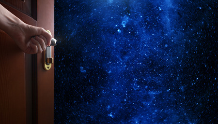 astrophotography: hand opens empty room door to Planet earth from the space.