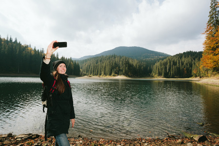 selfy: woman taking a selfy while hiking in the nature
