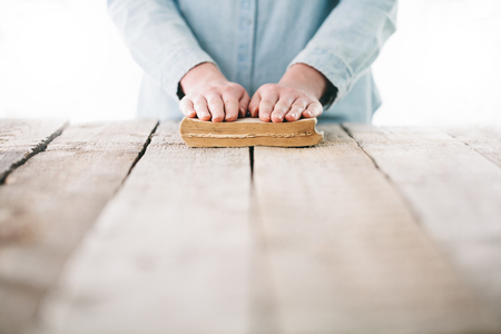 reverent: hands praying with a bible over wooden table