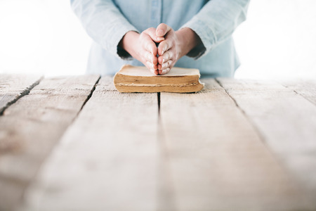Woman reading and praying over Bible Stock Photo