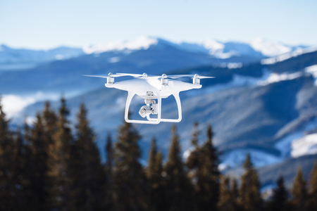 pilotage: drone copter flying with digital camera over the mountains Stock Photo