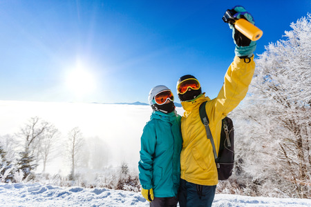 skiers: Skiers taking picture of themselves with smart phone over a mountain