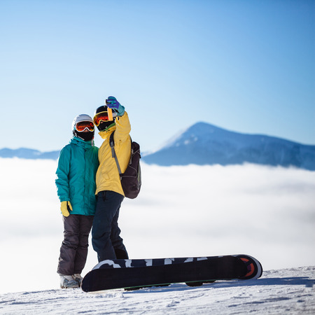 skiers: Skiers taking picture of themselves with smartphone over a mountain