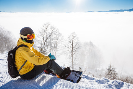 skying: Snowboarder sitting and looking at mountain chain in the background