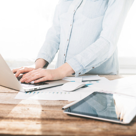 using the computer: Woman working on a laptop and tablet pc indoor on a wooden standing desk Stock Photo