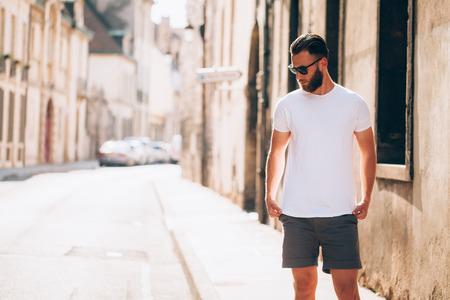 hipster beau modèle masculin avec barbe portant t-shirt blanc blanc avec espace pour votre logo ou un design dans un style décontracté décontracté