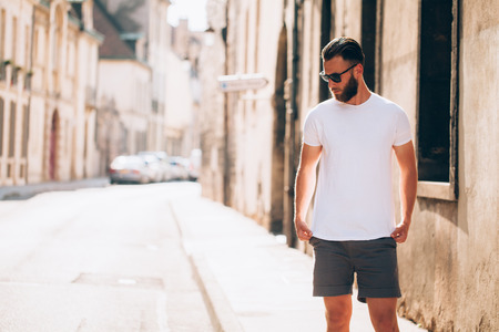 hipster modelo masculino guapo con barba vistiendo camiseta blanca en blanco con espacio para su diseño o diseño en estilo urbano casual