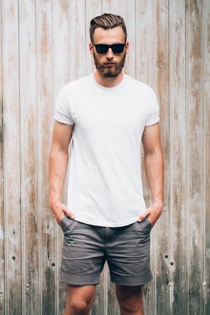 Hipster beau modèle masculin avec barbe portant un t-shirt blanc blanc avec un espace pour votre logo ou votre design en style urbain décontracté