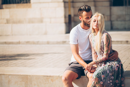 adult sexual: Blonde girl and Hipster handsome man with beard hugging and kissing on the city streets