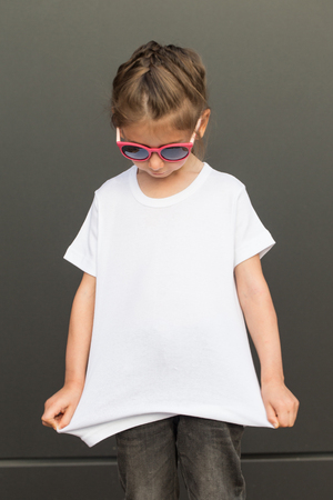 Girl kid wearing white blank  t-shirt with space for your logo or design in casual urban style Standard-Bild