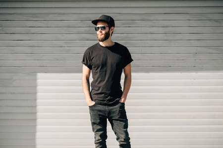 Hipster handsome male model with beard  wearing black blank  t-shirt with space for your logo or design in casual urban style Banque d'images