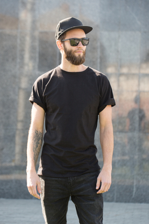 Hipster handsome male model with beard wearing black blank t-shirt with space for your logo or design in casual urban style Imagens