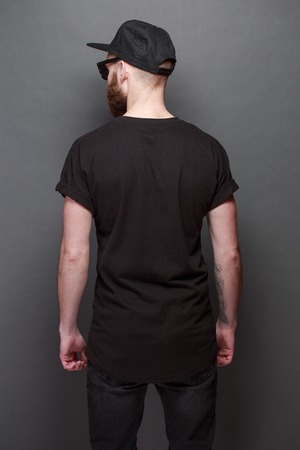 Hipster handsome male model with beard wearing black blank t-shirt with space for your logo or design over gray background Banque d'images