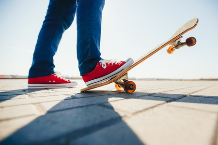 Skater and his feet on a skateboard Stock Photo
