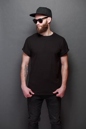 Hipster handsome male model with beard wearing black blank t-shirt with space for your design over gray background