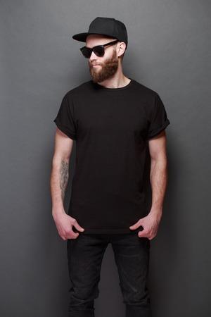 Hipster knap mannelijk model met baard die zwarte lege t-shirt met ruimte voor uw ontwerp over grijze achtergrond dragen Stockfoto