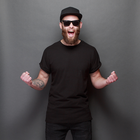 Hipster handsome male model with beard wearing black blank t-shirt with space for your design over gray background Reklamní fotografie - 96828115