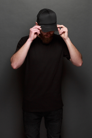 Hipster handsome male model with beard wearing black blank t-shirt and a black baseball cap with space Stock Photo